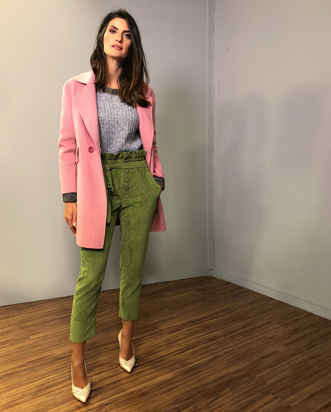 Isabella Fiorentino usa calça verde, blusa cinza e casaco rosa